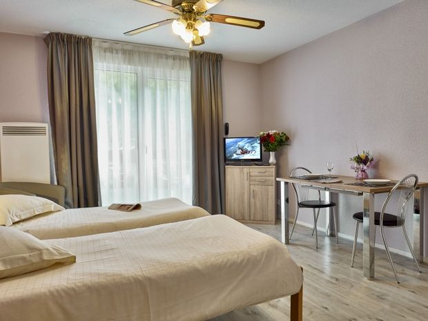 appart-hotel-residence-amneville-chambre-lit-tv-table-chaise-fenetre-rideau